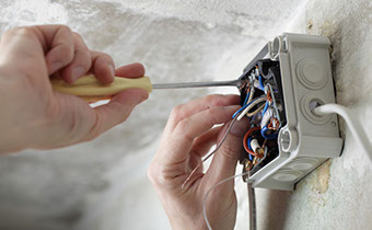 image of a person fixing some sockets and wiring